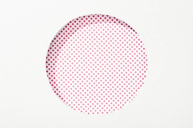 Cut out round hole in white paper on pink and white dotted background stock vector