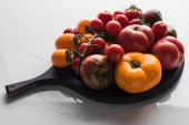 different tomatoes on wooden pizza pan on marble surface