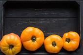 pohled na několik žlutých rajčat v dřevěné černé krabici