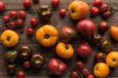 Draufsicht auf verstreute rote und gelbe Tomaten auf Holztisch