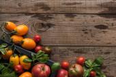pohled na rajčata a špenát v krabička na dřevěném stole