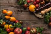 vista superiore di pomodori e spinaci in scatola vicino a mulino di pepe e mulino a sale su pezzo di tessuto su superficie di legno
