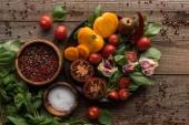 vista dallalto del piatto con spinaci, aglio e pomodori a fette vicino a pepe sparso e ciotole su tavolo di legno