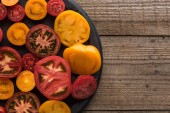 top view of sliced red and yellow tomatoes on pizza pan on wooden surface
