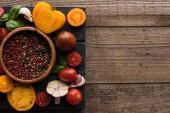 pohled na černý podnos s paprikou v misce, chilli papričkami, nakrájené rajčata a česnek na dřevěný stůl