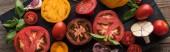 panoramatický záběr na nakrájené žluté a třešňová rajčata se špenátem, česnekem a chilli papričkami na černém dřevěném tácku