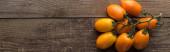 Panoramaaufnahme von gelben Tomaten auf Holztisch