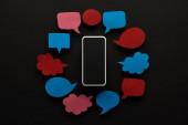 Nejlepší pohled na telefon smartphone na černém pozadí s prázdnými bublinami na řeč, koncept kyberšikanu