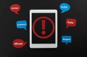 Fényképek tető kilátás-ból digitális tabletta-val felkiáltójel-ra képernyő-ra fekete háttér mellett beszéd buborék-val Online zaklatás szöveg