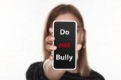 Fényképek az internetes zaklatás áldozatává vált szelektíven fókusza az okostelefon, nem zaklatott betűkkel, fehérre elszigetelt képernyőn