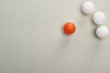 top view of balls symbolizing victim and abusers on grey background