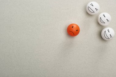 top view of balls with cruel and sad face expressions symbolizing victim and abusers on grey background