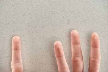 cropped view of man showing fingers symbolizing abusers and victim on grey background