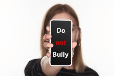 selective focus of victim of cyberbullying showing smartphone with do not bully lettering on screen isolated on white