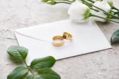 golden rings on white envelope near eustoma flowers on grey textured