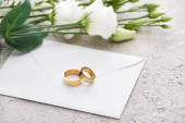 golden wedding rings on envelope near white eustoma flowers on textured surface