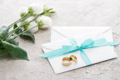 golden rings on white envelopes with ribbon near eustoma flowers on textured surface
