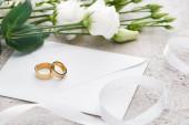arany Karikagyűrű fehér borítékon a közelben eustoma virágok és fehér szalag