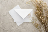 top view of piece of white envelope and card near flowers on textured surface