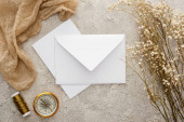 top view of white envelope and card near flowers, beige sackcloth and golden compass on textured surface