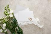Nejlepší pohled na svatební kroužky na prázdné kartě na bílém podkladu v blízkosti květin na texturované ploše
