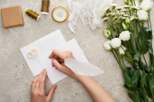 cropped view of woman writing on empty card near wedding rings, compass, cheesecloth, flowers and gift box on textured surface