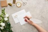 vágott kilátás nő írásban üres kártya közelében esküvői gyűrű, iránytű, olló, csévék és eustoma virágok textúrázott felületre