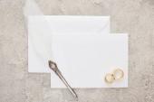 pohled na svatební kroužky a pero na bílou prázdnou kartu na texturované ploše