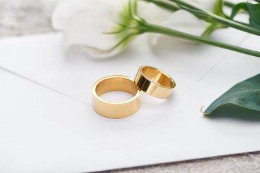 Golden wedding rings on white envelope near white flowers stock vector
