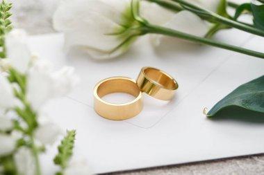 Selective focus of wedding rings on white envelope near white eustoma flowers stock vector