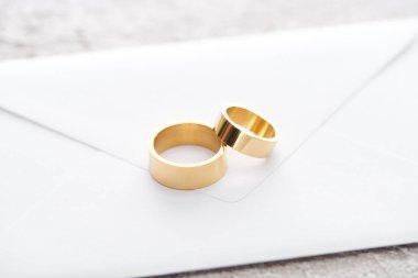 Golden wedding rings on white envelope on grey textured surface stock vector