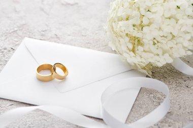 Golden rings on envelope near white ribbon and Hortense flower on grey textured surface stock vector