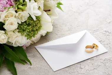 Wedding rings on white envelope near bouquet of flowers on textured surface stock vector