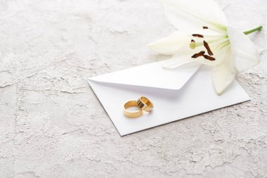 Two golden wedding rings on envelope near white lily on textured surface stock vector
