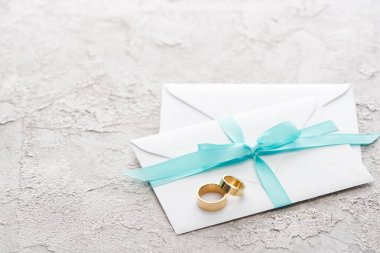 Two golden rings on white envelopes with blue ribbon on textured surface stock vector