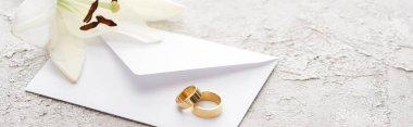 Panoramic shot of golden wedding rings on white envelope near lily flower stock vector