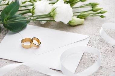 Golden wedding rings on white envelope near eustoma flowers and white ribbon stock vector