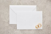 top view of golden wedding rings on blank invitation card on textured surface