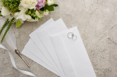 top view of wedding rings on envelopes near quill pen, white ribbon and bouquet on textured surface
