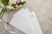 felülnézet jegygyűrűt a borítékon, közel a tollhoz, fehér szalaghoz és csokorhoz textúrázott felületre