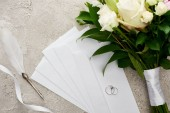 top view of silver rings on envelopes near bouquet, white ribbon and quill pen on grey textured surface