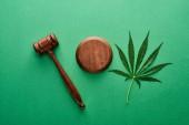 pohled na zelený list marihuany se dřevěným kladatelem na zeleném pozadí