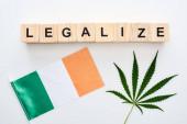 pohled na zelený konopový list a legalizaci písma na dřevěné kostky blízko irské vlajky na bílém pozadí
