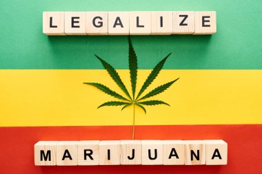 top view of cannabis leaf and wooden blocks with legalize marijuana lettering on Rastafarian flag background