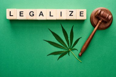 top view of green cannabis leaf, legalize lettering on wooden blocks and gavel on green background