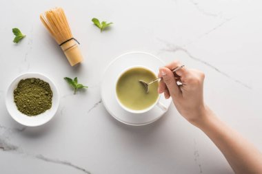 cropped view of woman with matcha matcha tea on table with whisk, powder and mint