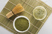top view of green matcha tea powder and drink in glass on bamboo mat