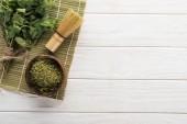 pohled na zelený matča Čajový prášek a máta na bambusové rohoži na bílém stole