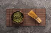 pohled na matča Čajový prášek se šlehací metou na bambusové rohoži na tmavém kamenném stole