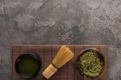 pohled na zelený matča čaj se šlehankou na bambusovou podložku na tmavém kamenném stole